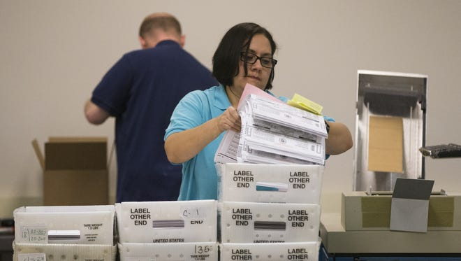 Early ballots are prepared on Monday for counting at the Maricopa County Recorder's Office in Phoenix. The counting of early ballots from Tuesday's election resumed here Thursday morning, with Pima County to begin counting early ballots again at 1 p.m., elections officials said.