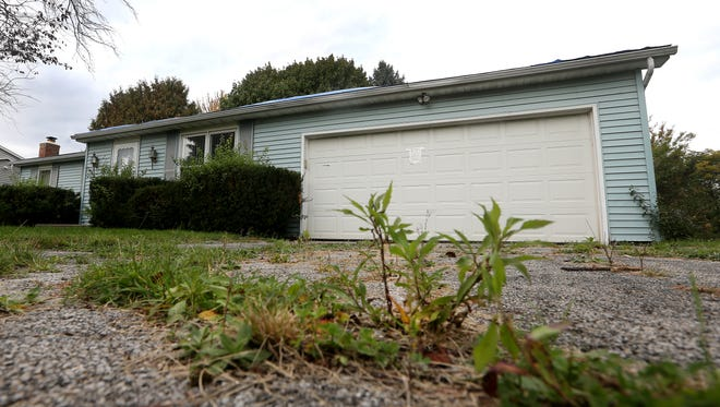 Weeds break through the driveway at the vacant house at 256 Drumcliff Way in Greece. Tarps also cover a deteriorating roof.