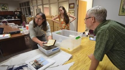 Jason Church (left) demonstrates how to safely recover a wet book at a workshop in 2013. Tips like this will be shared with flood victims at a free day-long workshop Thursday at the National Center for Preservation Technology and Training.
