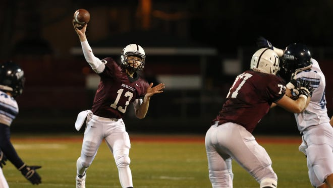 Dowling Catholic's Kurt Walding (13) throws the ball over Council Bluffs Lewis Central Friday. The Maroons will meet the rival Valley Tigers in the semifinals.