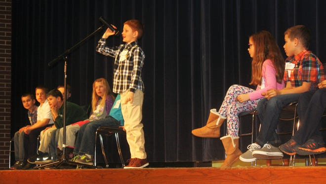 Third-grader Logan Jackson spells out a word during Monday's South Lyon District Spelling Bee at Millennium Middle School.