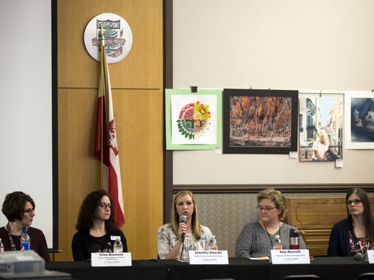 Panelist Jennifer Knecht, center, a school social worker for the Stevens Point Area Public School District, answers questions during the Kids in Crisis town hall in Stevens Point, Wis., Thursday, March 22, 2018.