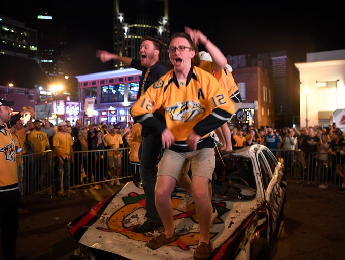 Fans jump on top of the demolition car after the Predators