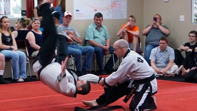 Spring Grove resident Ed Ogle, right, demonstrates a martial arts move on Mike Mitchell last Saturday at Global Martial Arts Academy in Hampstead, Md. Ogle was awarded his fifth-degree black belt at the end of the demonstration.