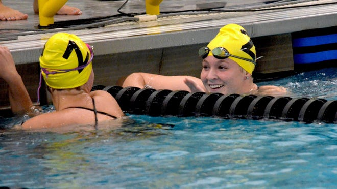 Zeeland's Rylee Fowler (right) reacts with a teammate after the 50-yard freestyle on Tuesday at Hamilton.