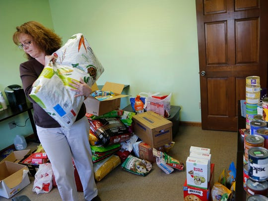 Dawn Berry sorts donated dog and cat food Monday, December