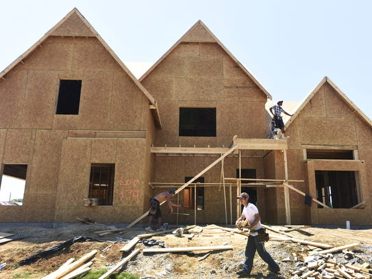 Workers build a home in the Boykin Lakes neighborhood