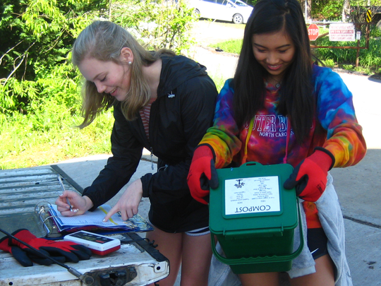 Summer Thoma, left, and Quin Ho check recyclables received at Owen High School.