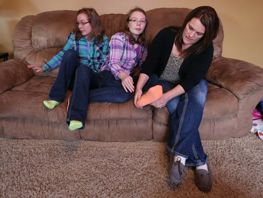 Kim Novy fixes her daughter Lindsey's sock, with Lindsey's