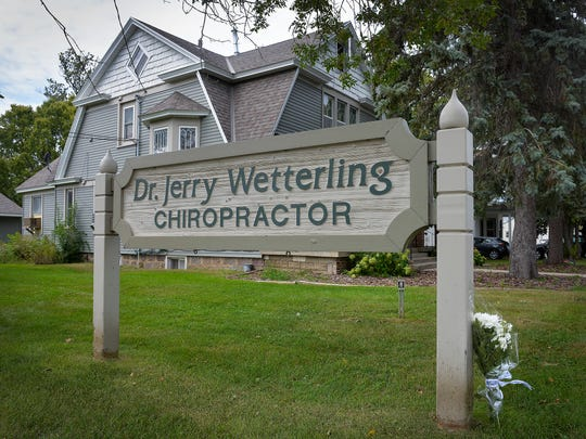 A single bouquet of flowers is rested on the sign for Dr. Jerry Wetterling's chiropractic office Saturday, Sept. 3, 2016.