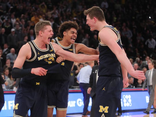 Michigan players Moritz Wagner, Jordan Poole and Jon Teske celebrate winning the Big Ten Tournament Championship 75-66 over Purdue on Sunday, March 4, 2018 at Madison Square Garden in New York.