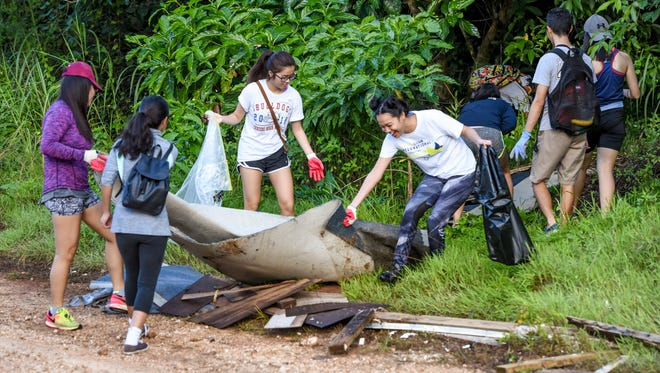 Students pull out discarded building material, they found in the jungle near Okkodo High School in Dededo, during the 23rd Annual Guam International Coastal Cleanup 2017 on Saturday, Sept. 16, 2017.