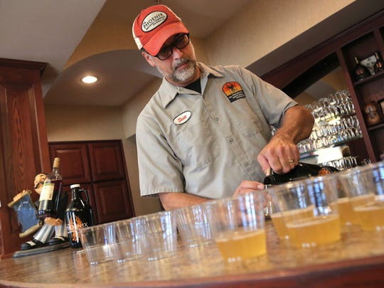 "Scott Cardwell, of the Phoenix Brewing Company, pours out samples of his new brew named ""Rhubarb"" in honor of his mother-in-law Barb Scofield at the Primrose Retirement community on Thursday."