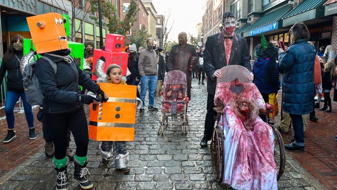 A family of robots watch as Ricky Sampson and his son Sean walk by in their gory costumes along the Essex Street Pedestrian Mall on Halloween afternoon, Saturday, Oct. 31, 2020.