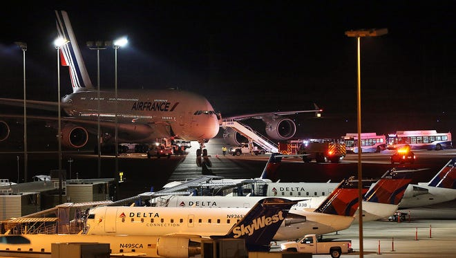Emergency vehicles are parked near an Air France plane that was diverted to Salt Lake City International Airport, Tuesday, Nov. 17, 2015, in Salt Lake City. Officials said two Air France flights bound for Paris from the U.S. had to be diverted because of anonymous threats issued after they took off, but both planes landed safely.