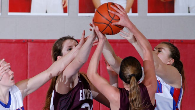 Mason's Katherine Rochon, left, and Hailee Ginter, right, and Eaton Rapids' Paige Boden, second from left, and Arianna Sysum vie for a rebound Tuesday, Feb. 21, 2017, in Mason, Mich.