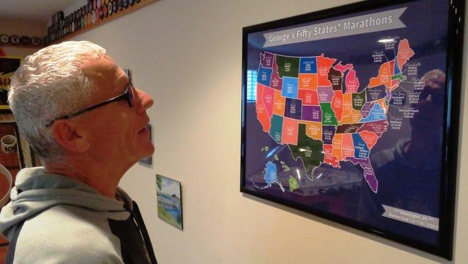 "George Brennock, 58, looks over the framed ""George's 50 States Marathons"" in his Loveland home."