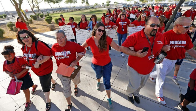 "Teachers walk arm-in-arm with students and parents into Tuscano Elementary School as they stage a ""walk-in"" for higher pay and school funding on April 11, 2018, in Phoenix. Teachers gathered outside Arizona schools to show solidarity in their demand for higher salaries staging ""walk-ins"" at approximately 1,000 schools that are part of a statewide campaign for a 20 percent raise and more than $1 billion in new education funding."