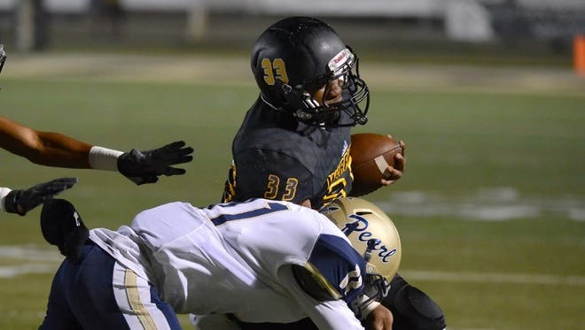 Oak Groves's Orlando Simon takes a hit from a Pearl defender Friday night during their game in Hattiesburg.