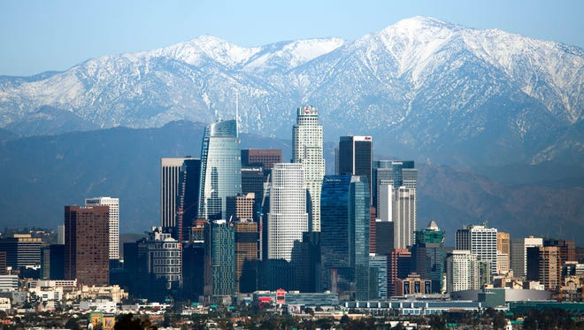 Snow-covered peaks on the San Gabriel mountains from recent storms frame the skyline of Los Angeles on Dec. 27, 2016.