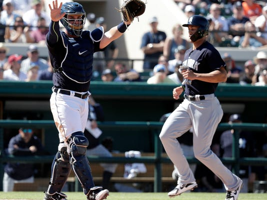 Detroit Tigers catcher James McCann, left, raises his arms to hold the throw to home as New York Yankees' Giancarlo Stanton scores on a base hit by Aaron Hicks during the fourth inning in a spring training exhibition baseball game, Tuesday,March 6, 2018, in Lakeland, Fla. (AP Photo/John Raoux)