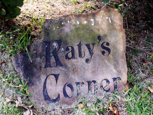 """A stone reading """"Katy's Corner"""" sits in the yard of"""