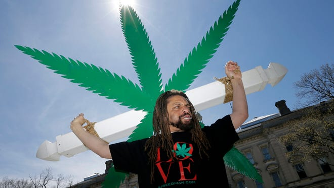 Ed Forchion, a pro-marijuana activist known as NJ Weedman, carries a large cross with huge likeness of a marijuana leaf as he walks in front of the New Jersey Statehouse in Trenton, N.J., Sunday, April 20, 2014.