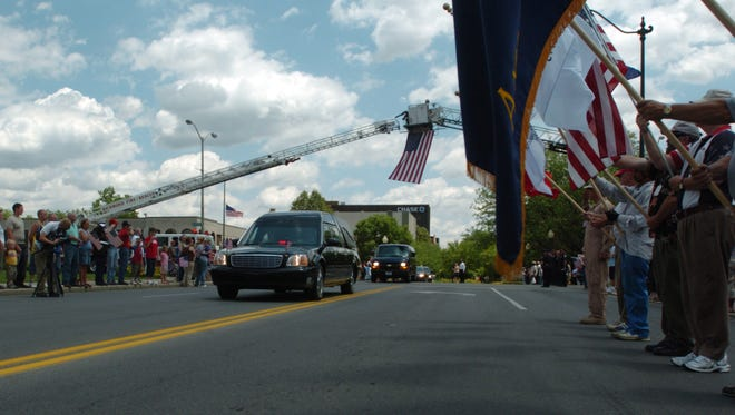 The hearse carrying the body of Lance Cpl. Layton Crass passes citizens along Richmond's East Main Street on Thursday, June 19, 2008.