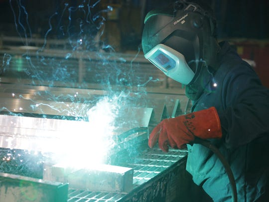 Ed Radomski spot welds aluminum strips to a frame before they are anodized at Linetec in Wausau.