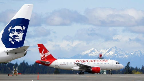 FILE - In this Monday, April 4, 2016, file photo, a Virgin America plane taxis past an Alaska Airlines plane waiting at a gate, at Seattle-Tacoma International Airport in Seattle. Alaska said Wednesday, March 22, 2017, that it will retire the Virgin brand, probably in 2019. Alaska announced in 2016, that it was buying Virgin, but CEO Brad Tilden held out hope to Virgin fans that he might keep the Virgin America brand, and run it and Alaska as separate airlines under the same corporate umbrella.