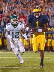 FILE - In this Oct. 20, 2004, file photo, Michigan wide receiver Braylon Edwards (1) outruns Michigan State cornerback Aston Watson (12) for a touchdown during the third overtime period of an NCAA college football game at Michigan Stadium in Ann Arbor, Mich. Michigan versus Michigan State on Saturday, Oct. 17, 2015, holds more than provincial interest. The Spartans are No. 7 and the Jim Harbaugh-led Wolverines are No. 12. (AP Photo/Carlos Osorio, File)