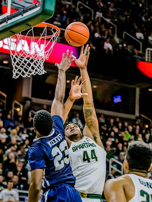 Nick Ward ,44, of MSU lays the ball up and in over Oral Roberts defender Emmanuel Nzekwesi to extnd the MSU lead to 66-61 late in the 2nd half of their game Saturday December 3, 2016 in East Lansing.  KEVIN W. FOWLER PHOTO