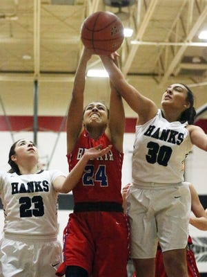 Alysse Blair, 30, of Hanks fights for a rebound with Bianca Avalos, 24, of Bel Air Friday night at Hanks. At left is Valerie Hernandez, 23 of Hanks. The Knights out scored the Highlanders 33-29.