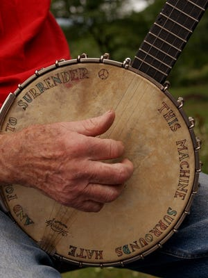 Pete Seeger performs a song on his banjo.