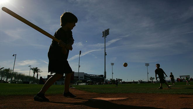 Kids play wiffle ball on a miniature field at Goodyear Ballpark.