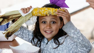 Seven-year-old Tahi Luke of Pewaukee enjoys an ear of sweet corn during the 23rd annual Pewaukee Kiwanis Beach Party at Pewaukee Beach on Friday, June 22, 2018. The two-day event, held in conjunction with the Lake Country Clean Water Festival, features live music, food, beverages and a variety of waterfront activities.