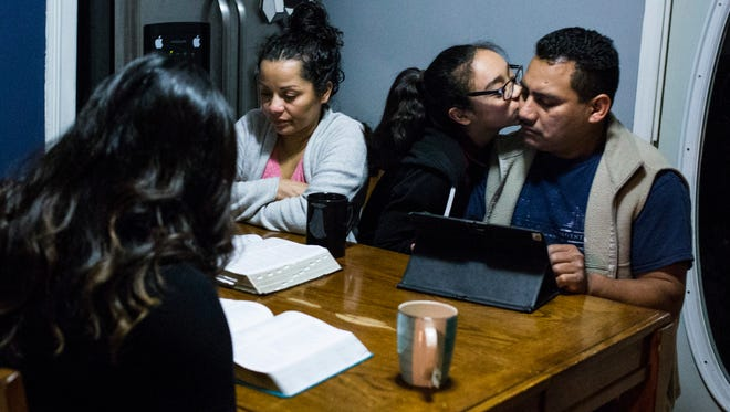Diana Hernandez, greets her father Mario, as her mother, back left, Matilde, and sister, front left, Estrella, read scripture before she prepares to go to school from their home in Detroit on Tuesday, March 28, 2017.