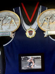 Mason Loupe's wrestling awards and jersey hang in Melanie