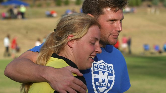 Madison Academic coach Chris Baker hugs Haleigh Smith after defeating Trinity Christian Academy during a District 15 A-AA semifinal at Jackson Christian in Jackson, Tenn., on Tuesday, Oct. 11, 2016.