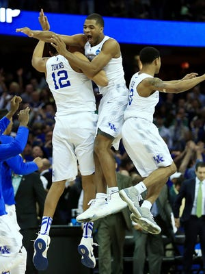 Kentucky Wildcats forward Karl-Anthony Towns (12) and guard Aaron Harrison (2) and guard Tyler Ulis (3) jump in the air after the game against the Notre Dame Fighting Irish in the finals of the midwest regional of the 2015 NCAA Tournament at Quicken Loans Arena. Kentucky won 68-66.