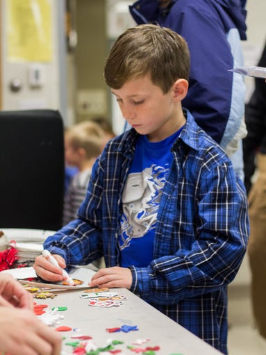 Cole Goodman, 8, adds final touches onto his artwork
