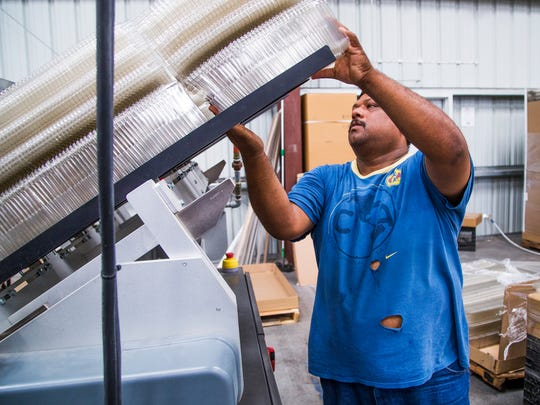 Green machine operator Manny Carranza loads egg cartons made from recycled plastic water bottles into the machine at Hickman's Family Farms Aug. 29, 2017. The company is changing some of its chicken pens to cage-free facilities, and additionally is making egg cartons from recycled materials.