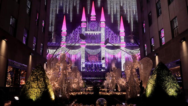 Christmas angels frame the side of the Saks Fifth Avenue store which was aglow with lights across from Rockefeller Center during the 84th annual Rockefeller Center Christmas tree lighting ceremony, Wednesday, Nov. 30, 2016, in New York. The 94-foot tall Norway spruce is covered with 50,000 multicolored LED lights.