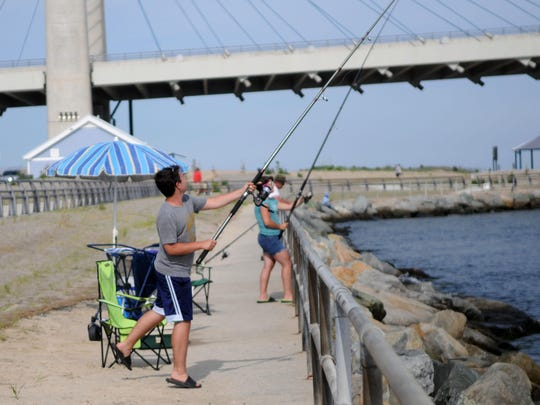 A young fisherman tosses his line out into the Indian River Inlet.