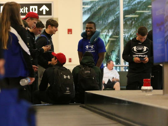 Isreal Anis, center, laughs with his teammates as they wait for baggage claim at RSW Airport in Fort Myers on Sunday, Sept. 4, 2016. Community School of Naples football players arrived in Fort Myers Sunday evening after making the nearly 5,000-mile trip to Dublin, Ireland for the American Football Showcase.