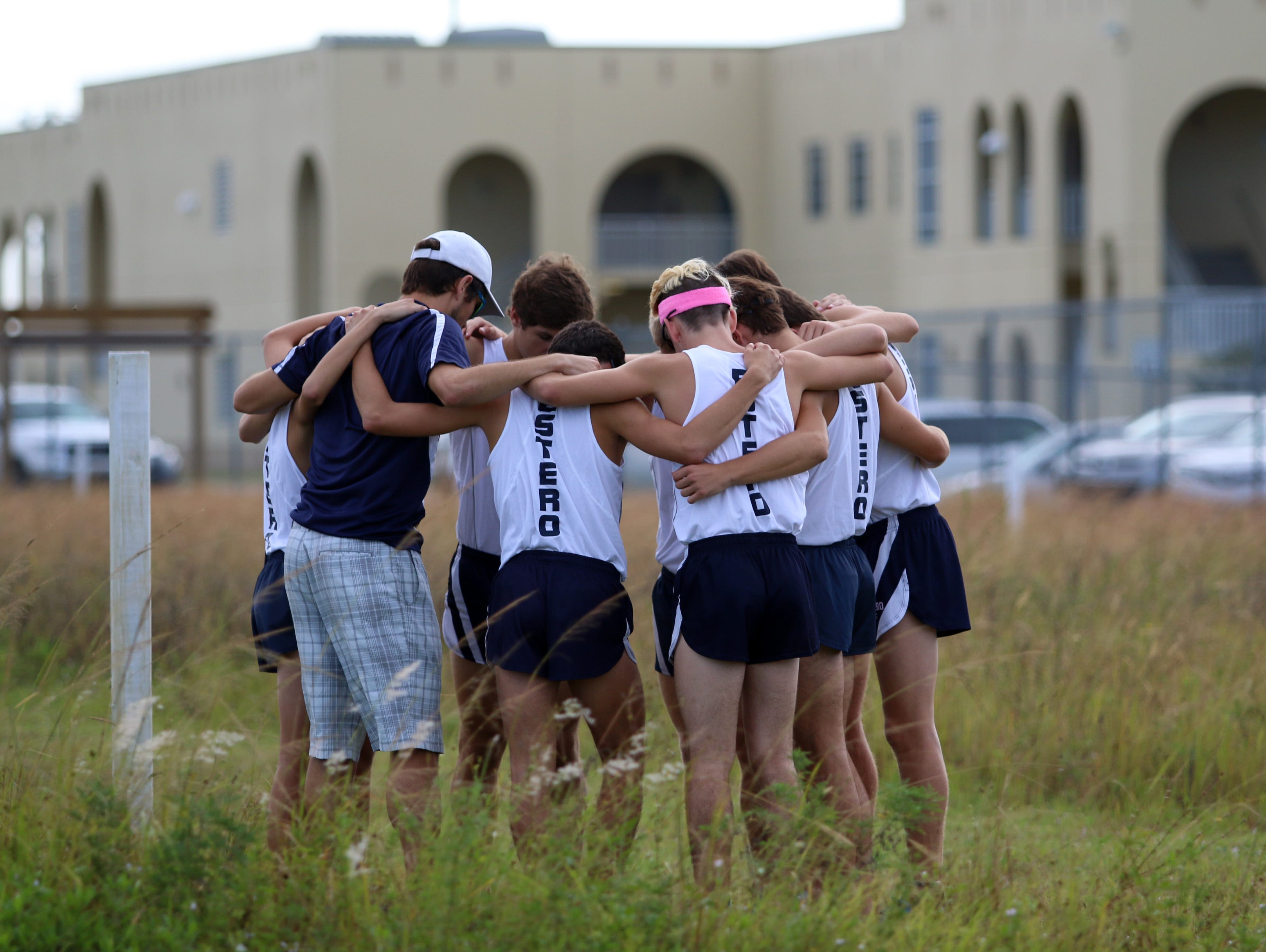 The Estero boys cross country team huddles before the race at Thursday morning's District 3A-12 meet at Palmetto Ridge High School in Naples,