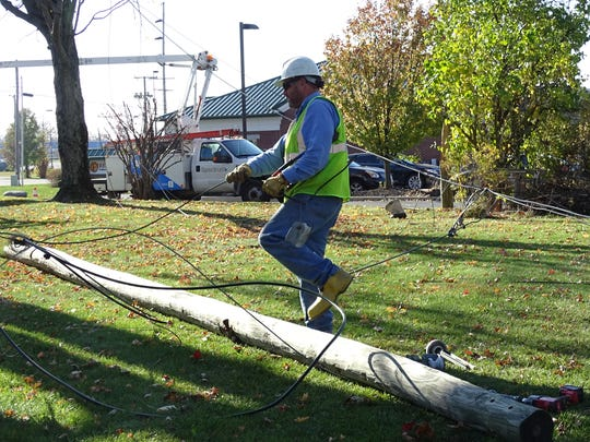 An AEP employee pulls power lines across a Bucyrus