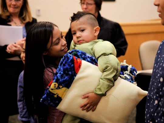 Elena Monge, left, holds Lucas Monge following an adoption hearing before District Judge Sandra Price on Nov. 14 in Farmington District Court.
