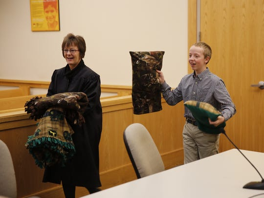 District Judge Sandra Price, left, and Ryan Levin carry blankets and pillows given to Ryan and his brother Charles Levin following an adoption hearing on Nov. 14 at Farmington District Court.