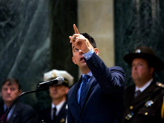 Governor Scott Walker explains how the Wisconsin Law Enforcement Memorial is made from the same granite that is used inside the State Capitol building during the ceremony in Madison, Wis., Friday, May 11, 2018.